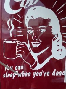 """כדי להחזיק מעמד במירוץ החיים, אנו לעיתים שותים עוד כוס קפה ו..עוד אחת. לקפה יש יתרון מיידי. הוא נותן לנו עירנות  ואנרגיה מיידיית. אך בשימוש ארוך, הוא שוחק את בלוטת האדרנל והויטמינים החיוניים,וגורם לעייפות גבוהה יותר. בתמונה פירסומת לקפה כפי שנצפתה בשוק מאוור בברלין. בכיתוב """" You can sleep when you""""re dead."""